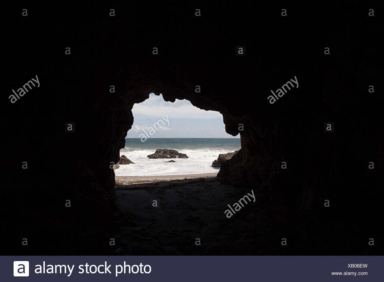 View through cave hole toward sea - Stock Image