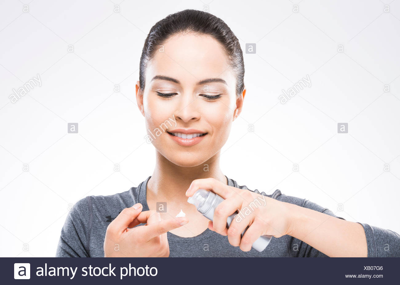 Young woman applying moisturizer - Stock Image