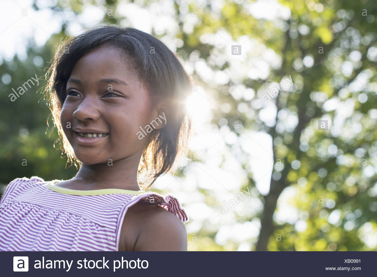 A young girl with short hair in a striped sundress smiling - Stock Image