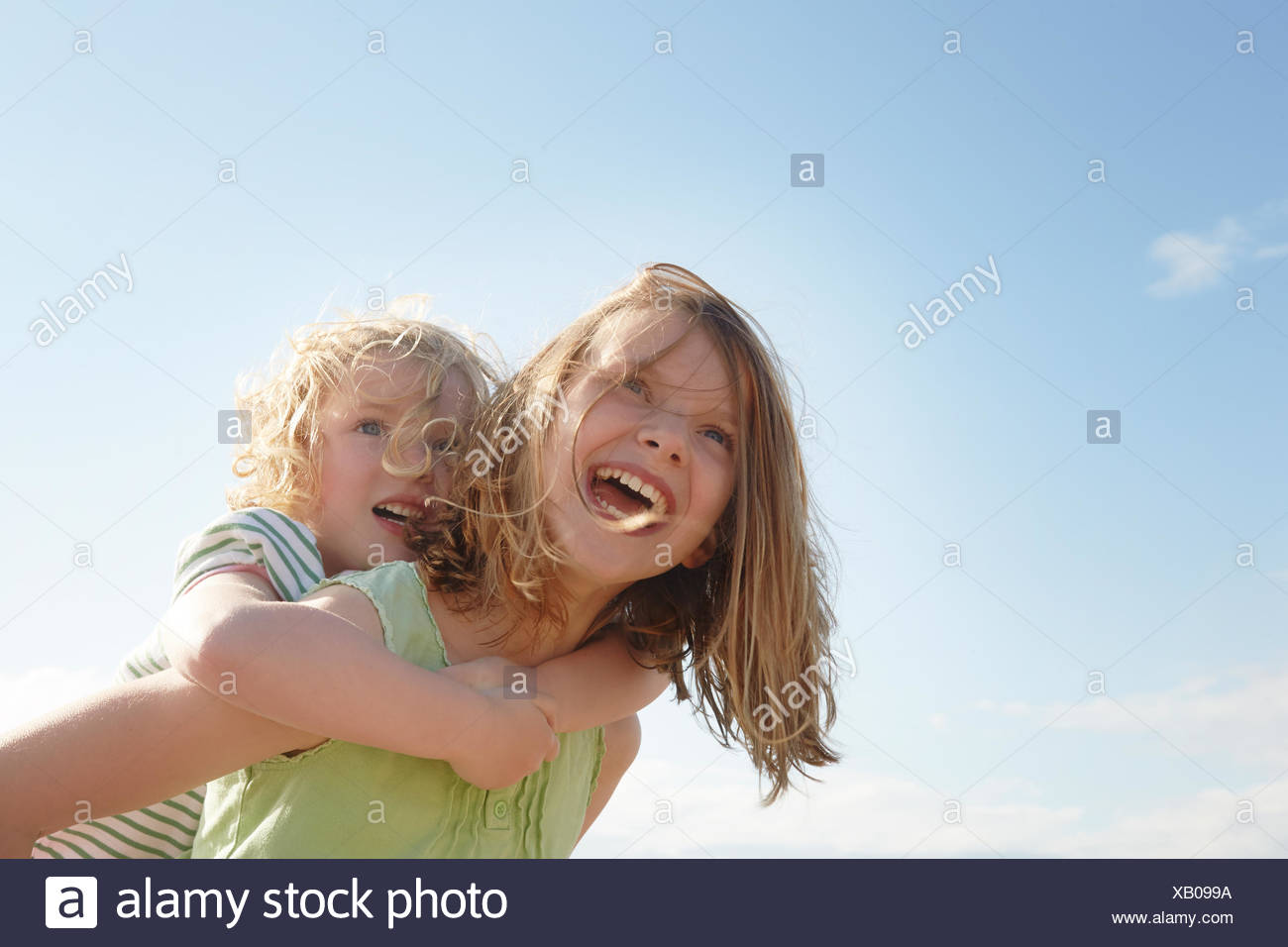 Low angle view of girl giving sister piggy back at coast - Stock Image
