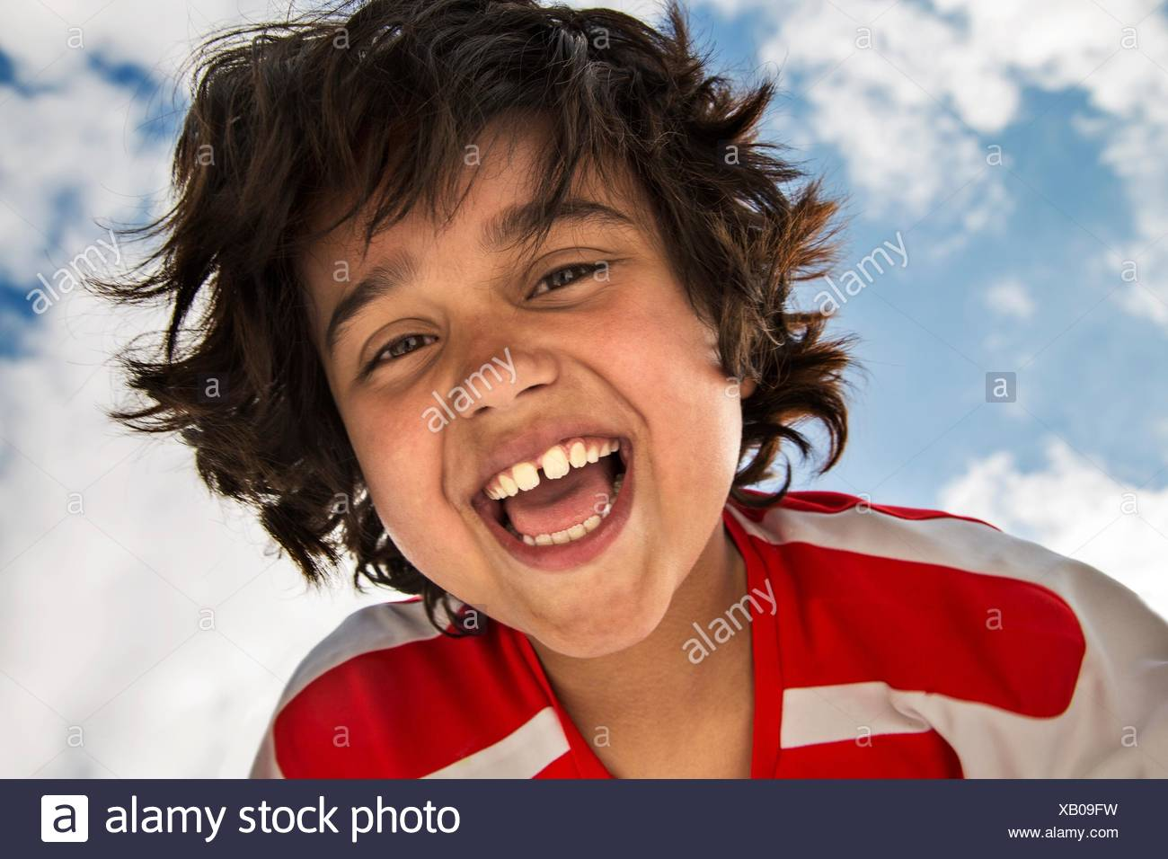 Low angle portrait of smiling boy in front of sky - Stock Image