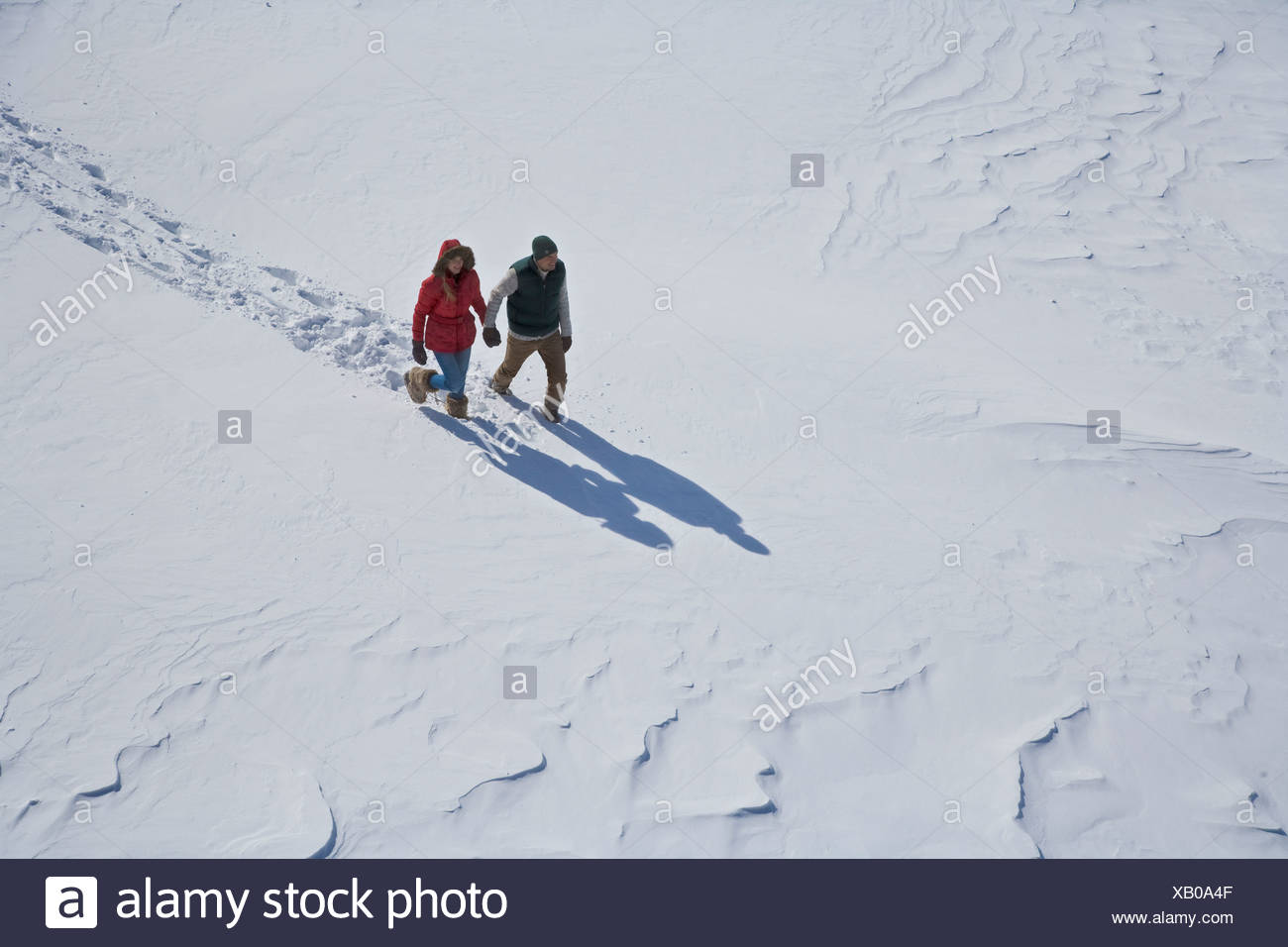 High angle view of young couple walking in snow - Stock Image