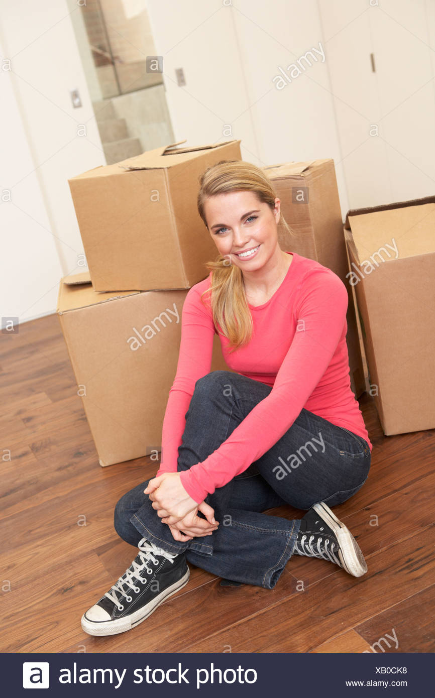 Young woman on moving day sitting on floor among cardboard boxes - Stock Image
