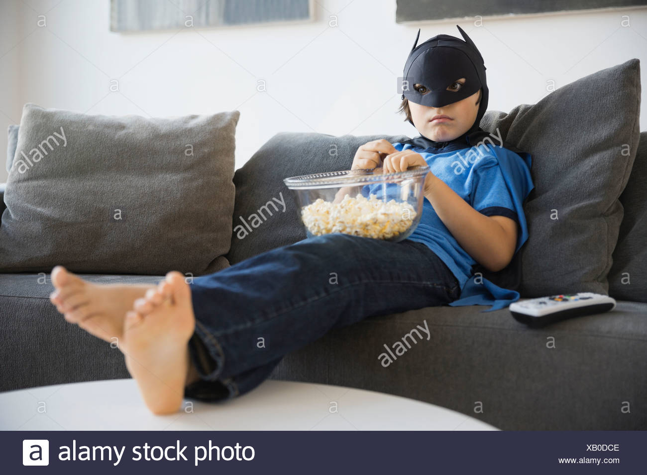 Boy dressed in superhero costume watching TV at home - Stock Image