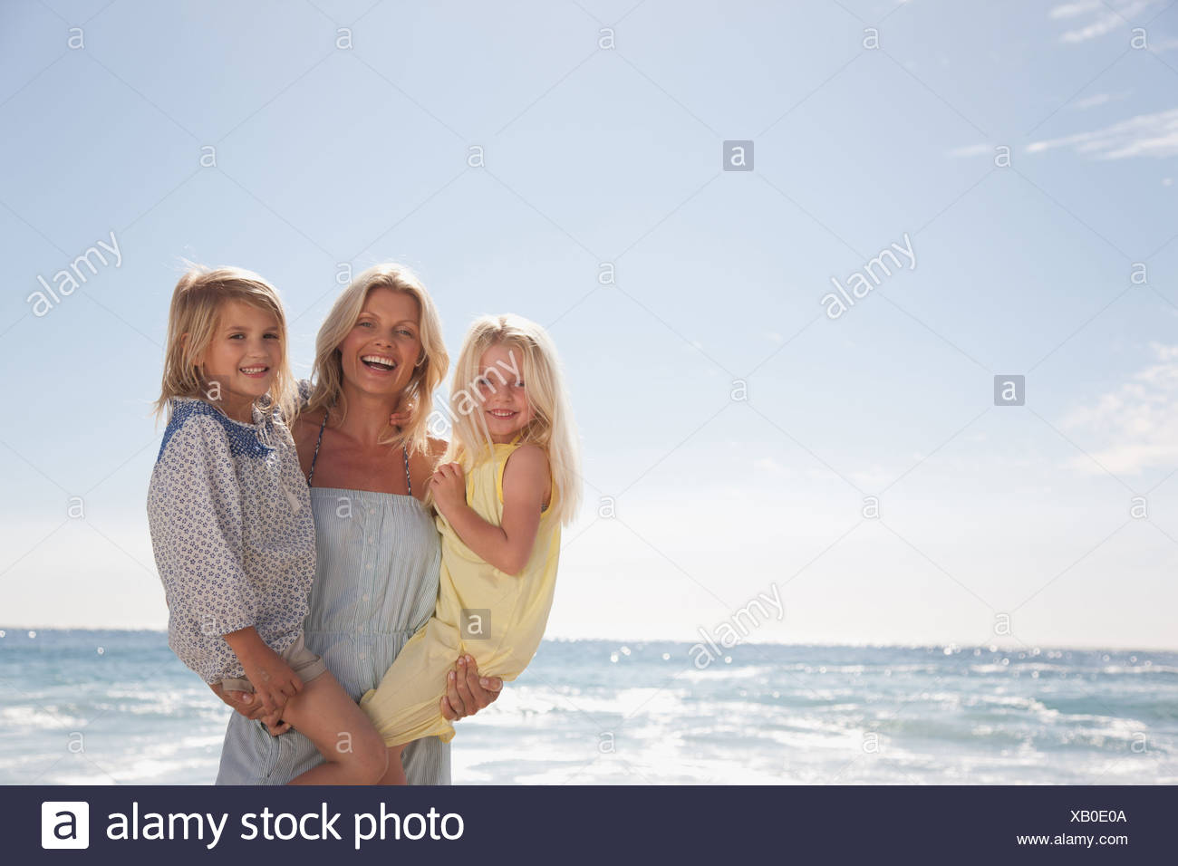 Mother holding daughters on beach - Stock Image