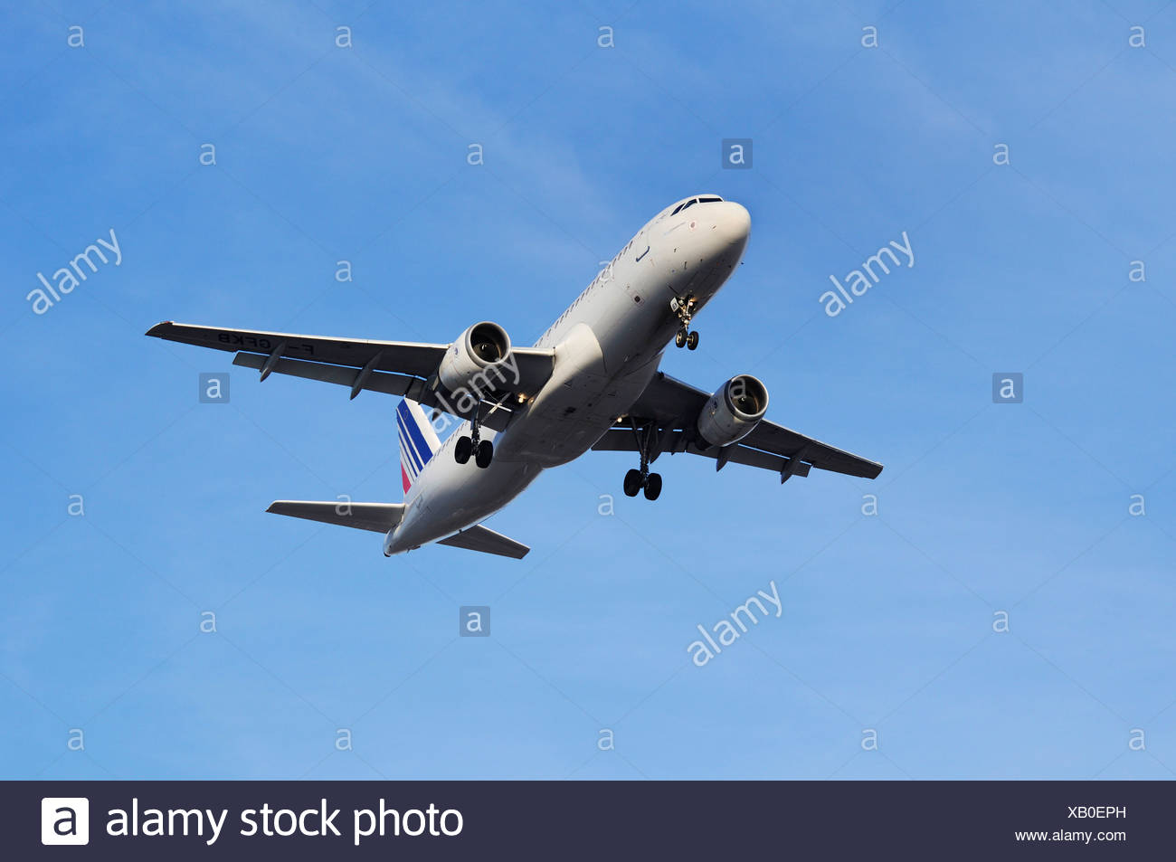 Commercial aircraft, Air France KLM, climbing against a light-blue sky, perspective from diagonally below - Stock Image