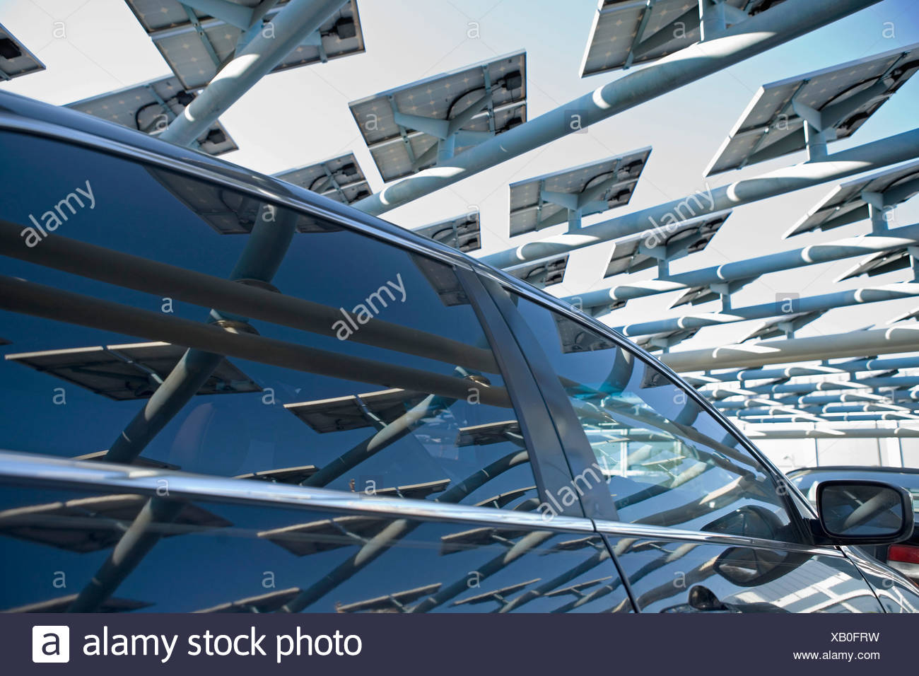 Solar panels reflected in car window - Stock Image