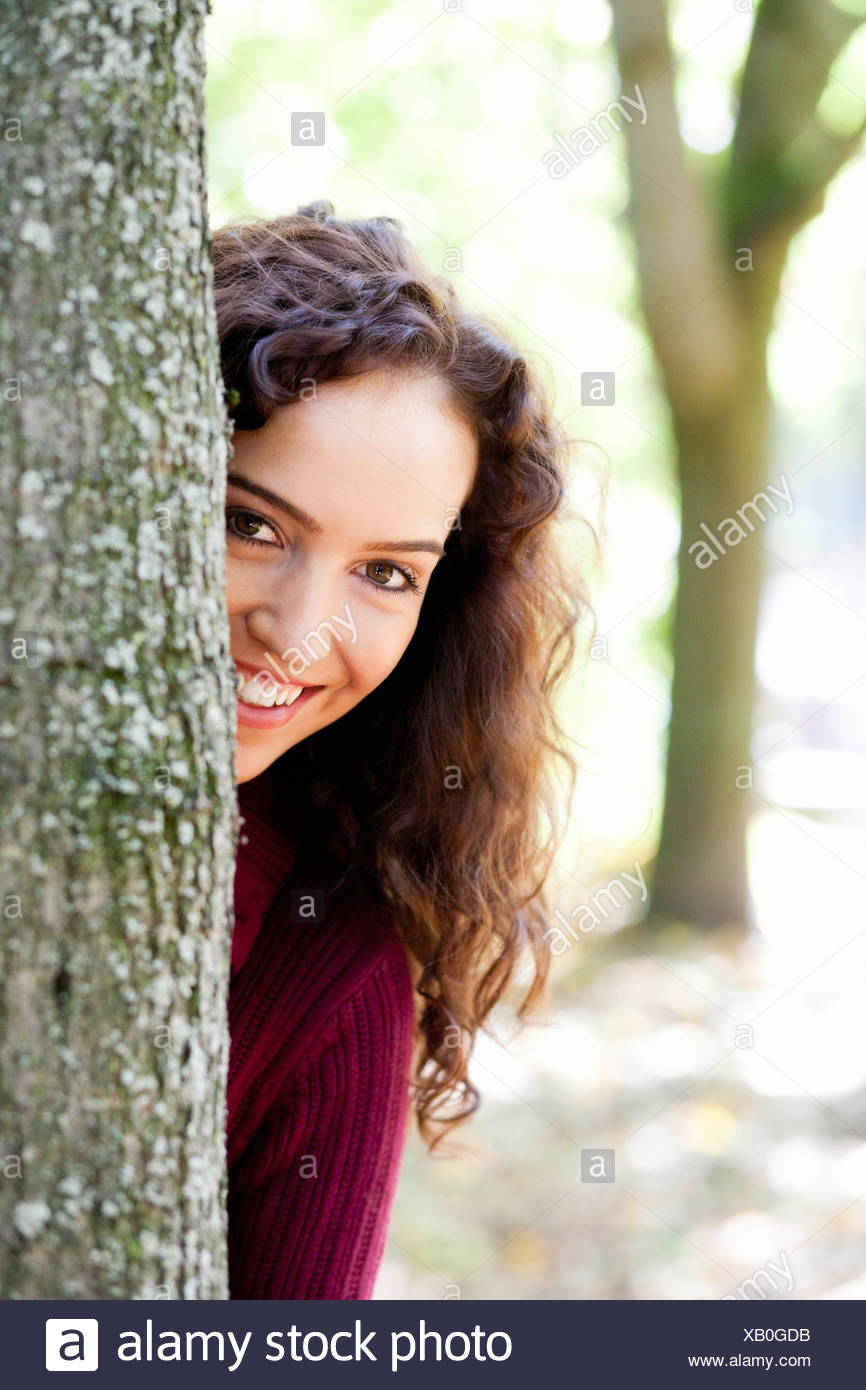 young woman hiding behind tree - Stock Image
