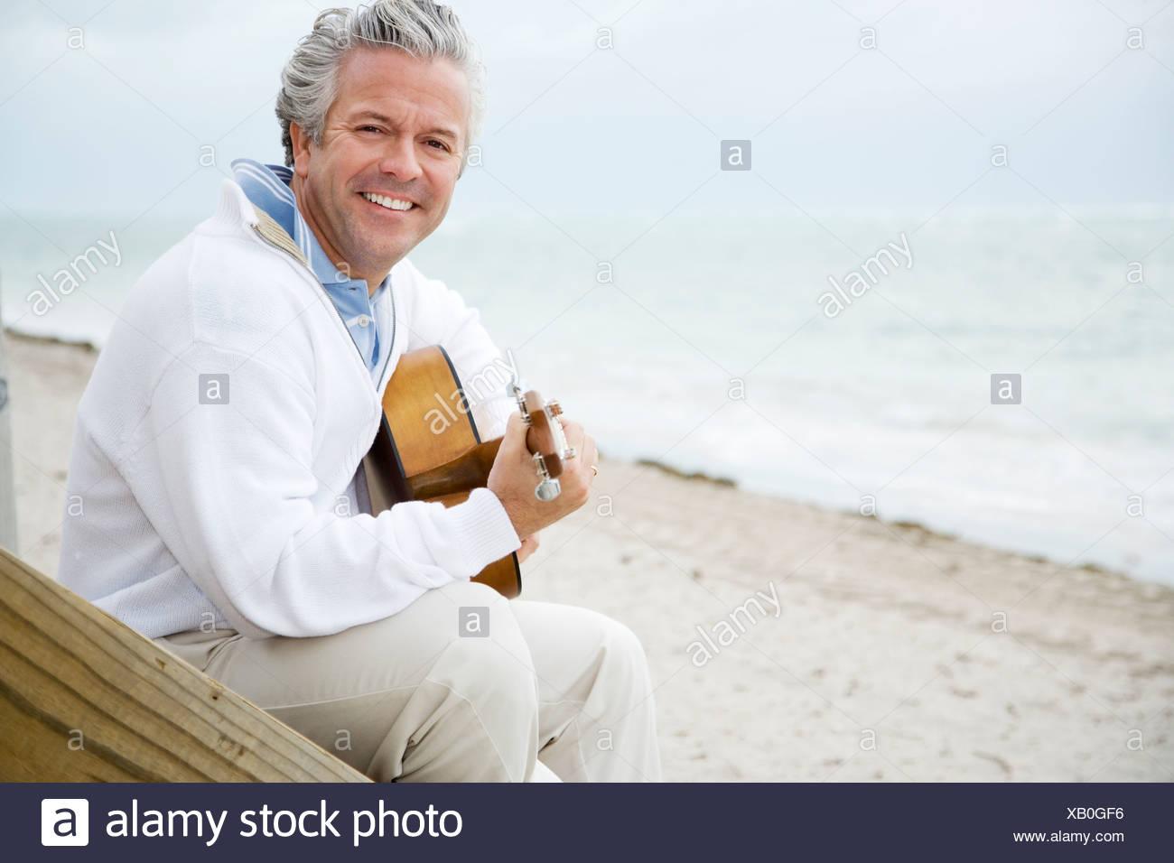 A senior man playing a guitar - Stock Image