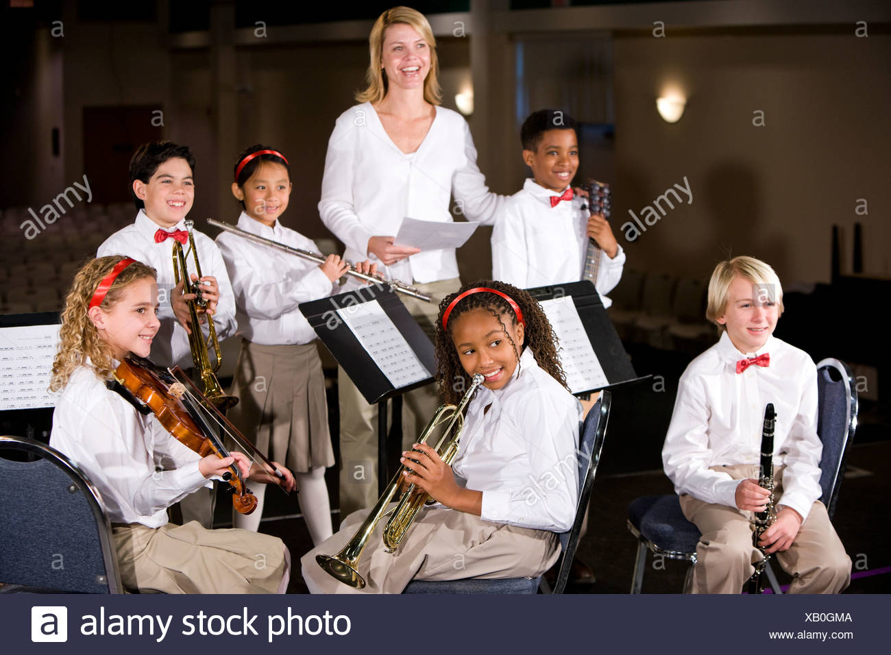 School children playing musical instruments in band with teacher - Stock Image