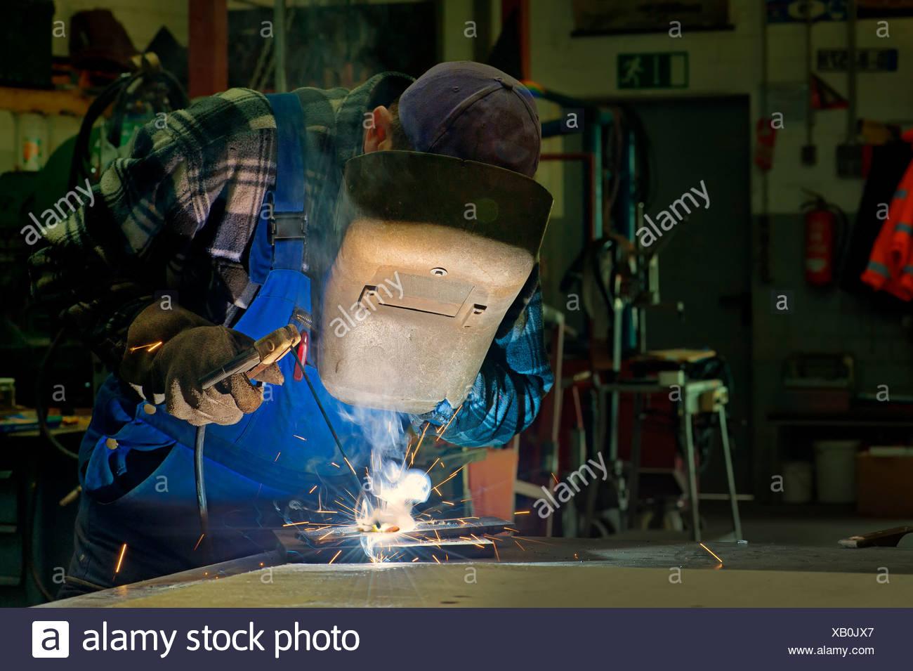 Welder doing electric welding in his workshop - Stock Image