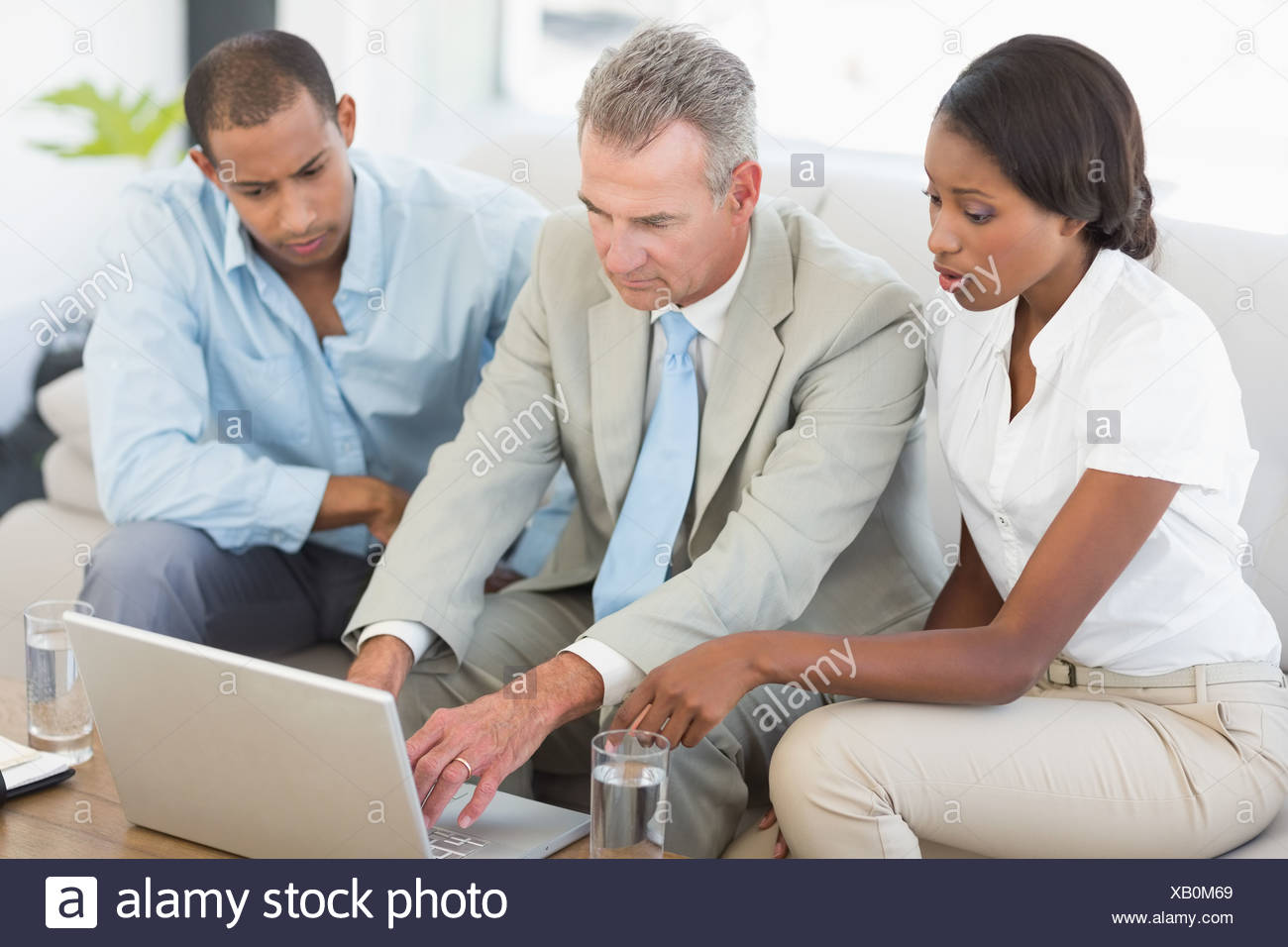 Salesman showing something on laptop to couple on sofa - Stock Image