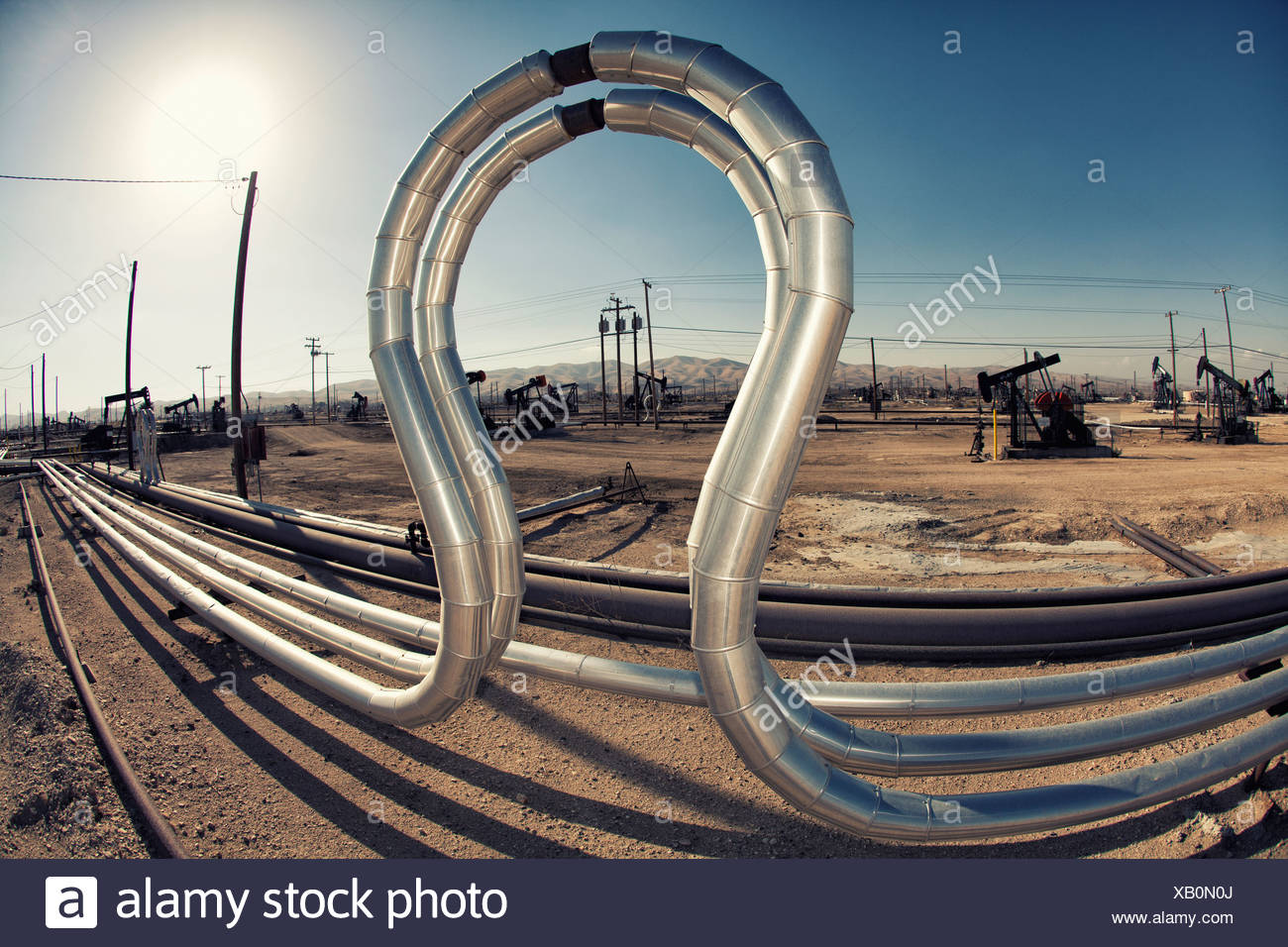 Curved pipes in oil field - Stock Image