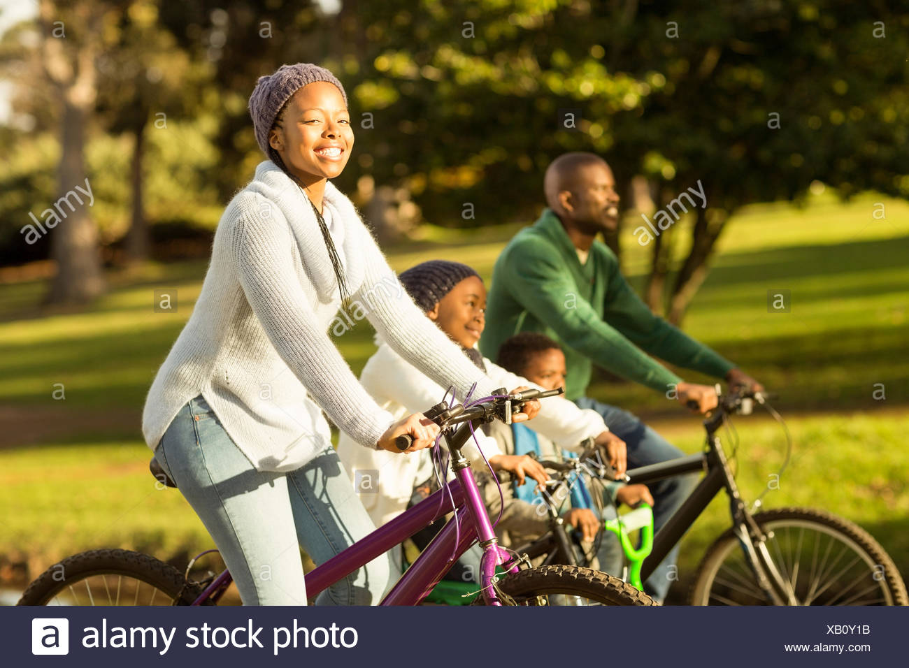 Side view of a young family doing a bike ride Stock Photo
