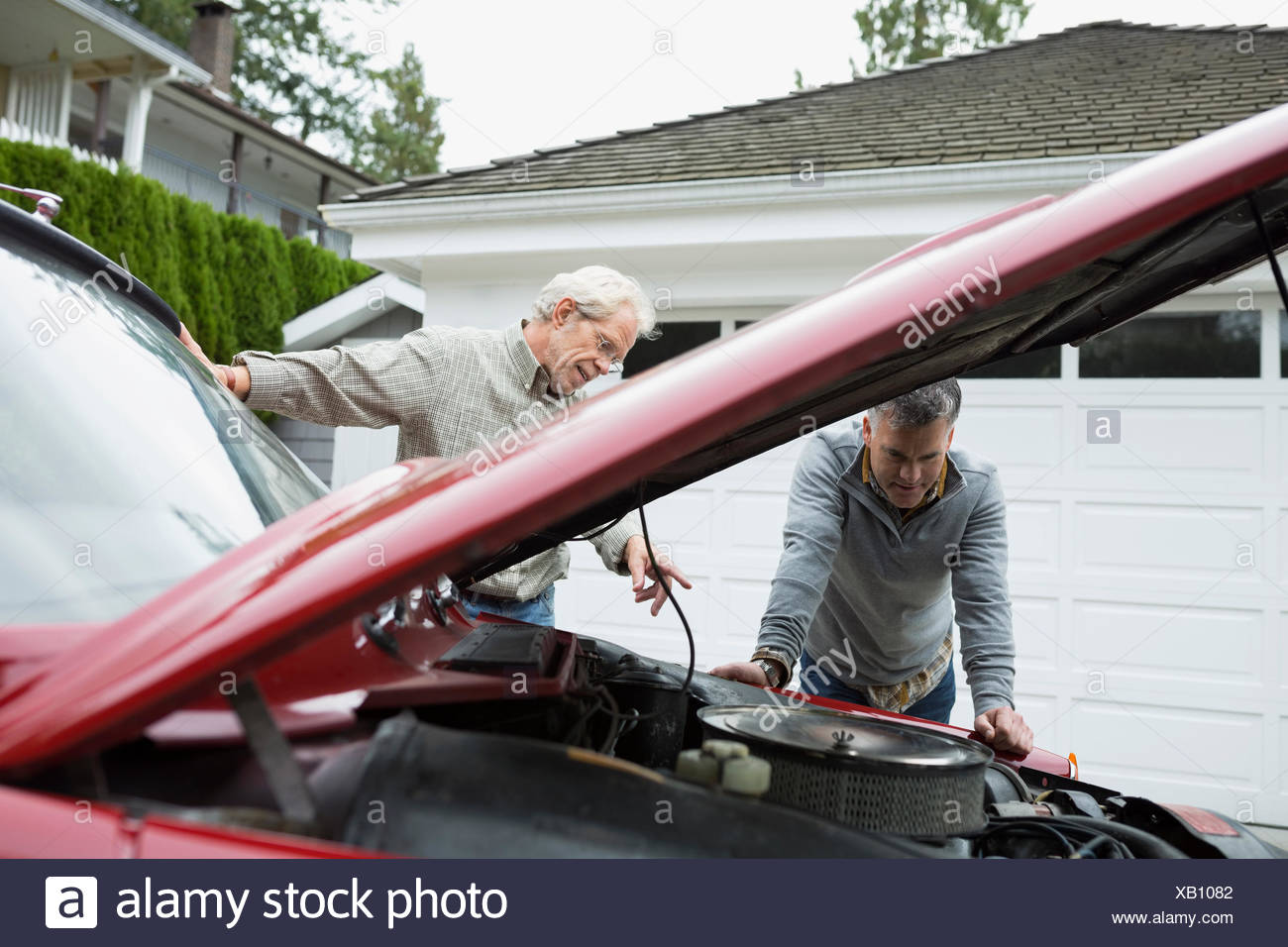 Father and son checking engine classic car driveway - Stock Image