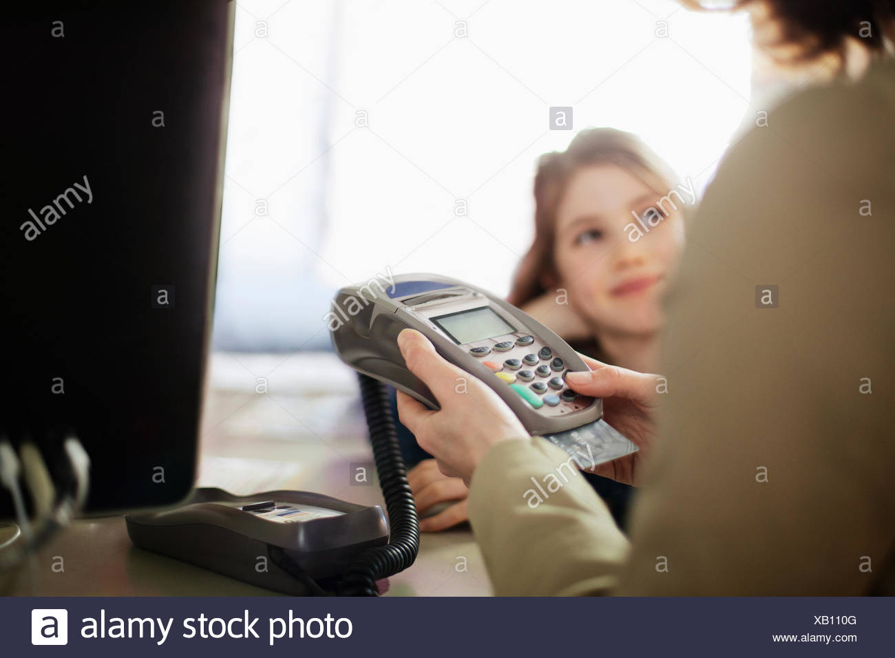mom and daughter paying for purchase - Stock Image