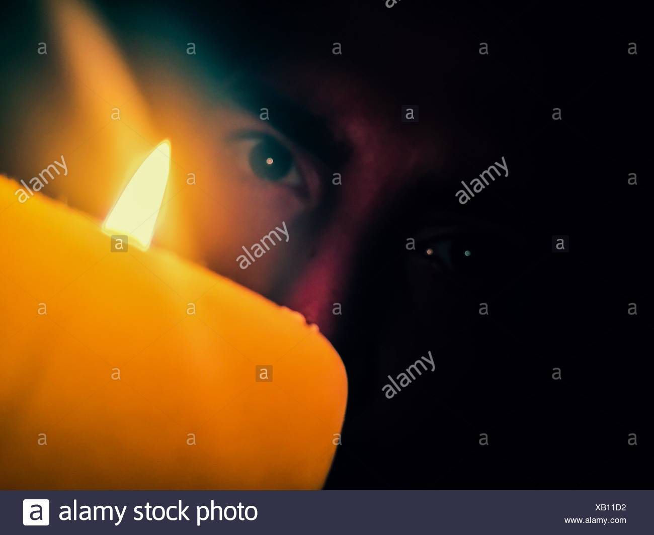 Portrait Of Man In Front Of Lit Candle In Darkroom - Stock Image