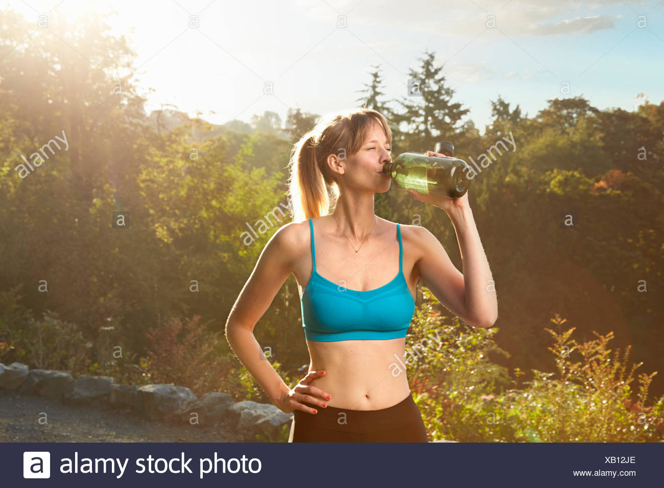 Mid adult female runner taking a water break in park - Stock Image