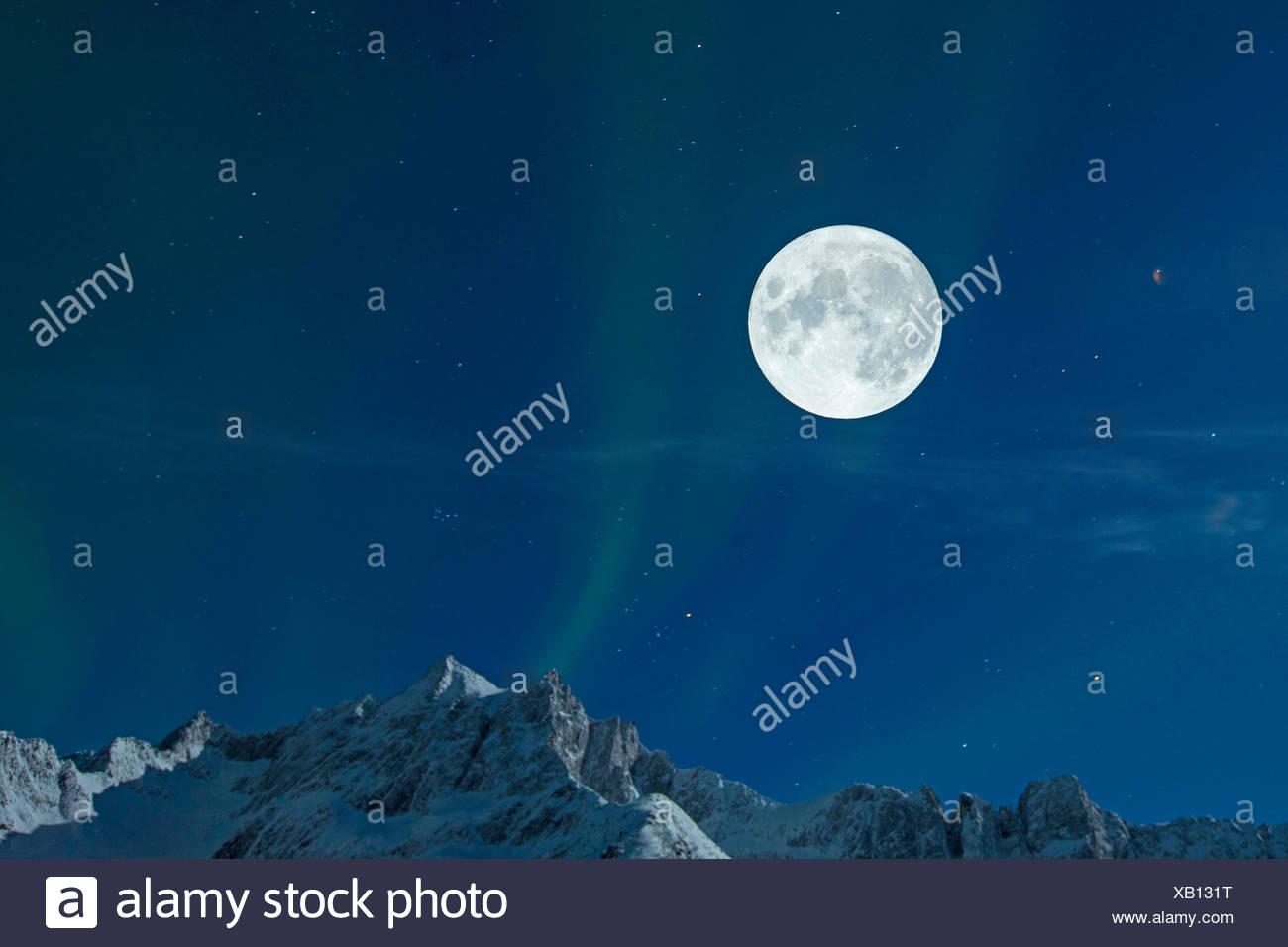 Vollmond mit Sternenhimmel und Nordlicht ueber Berggipfeln, Norwegen, Troms, Senja   full moon with starry sky and polar light o - Stock Image