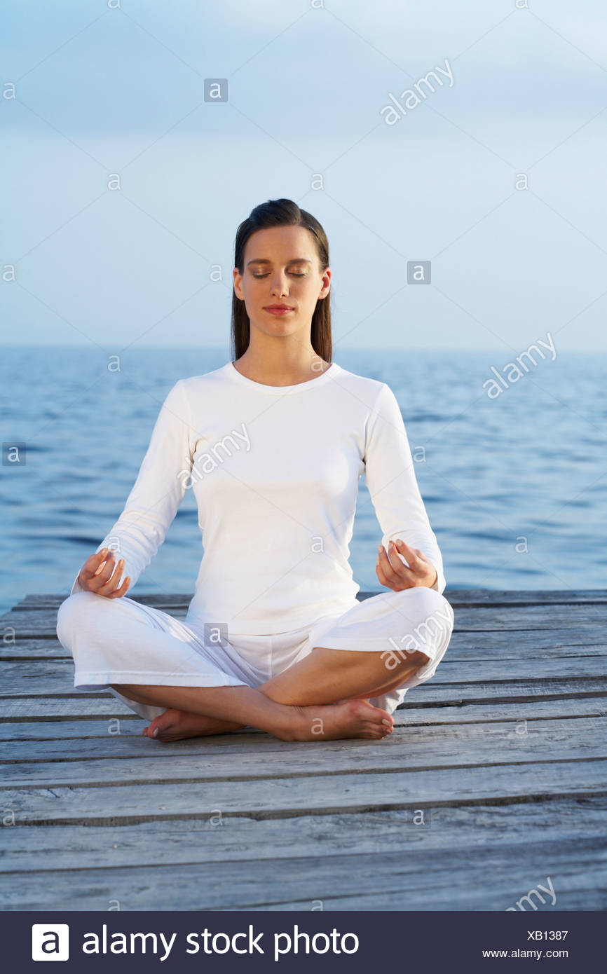 Young woman with eyes closed sitting cross legged on a dock. - Stock Image
