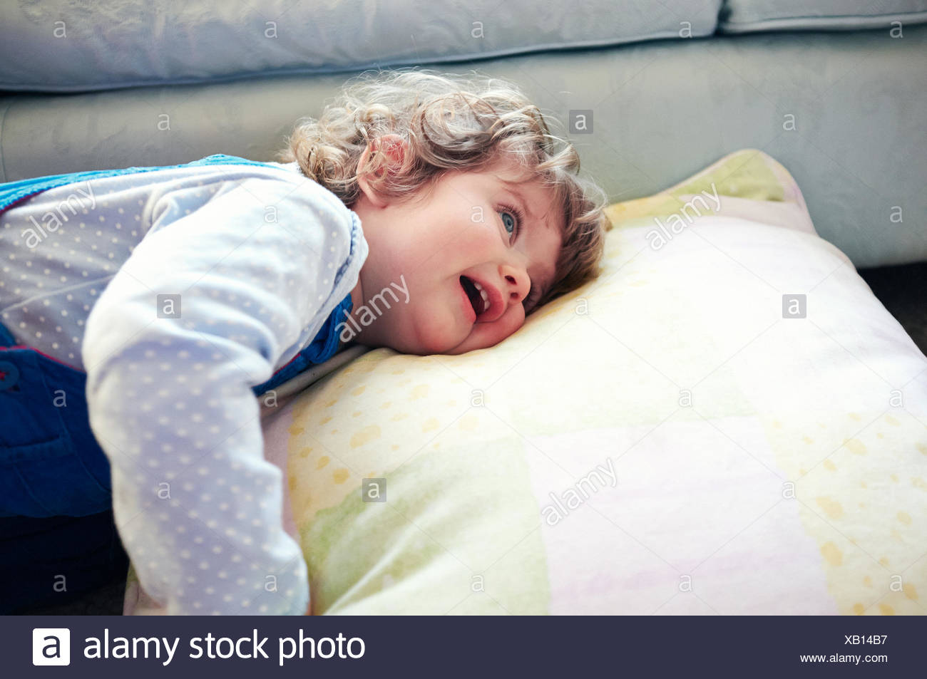 Girl laying on pillow in living room Stock Photo