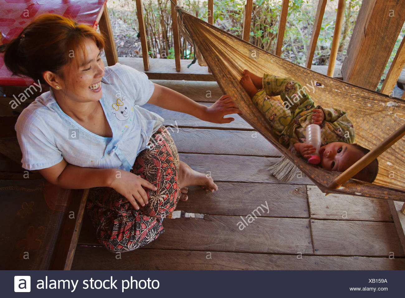 a mother rocks her baby lying in a hammock, Burma, Kengtung, Kyaingtong - Stock Image