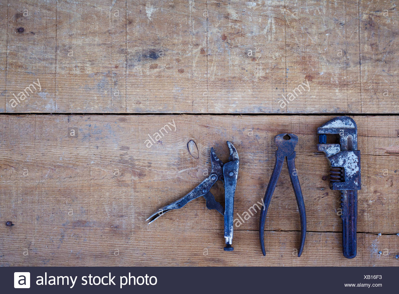High Angle View Of Rusty Tools On Wooden Table - Stock Image