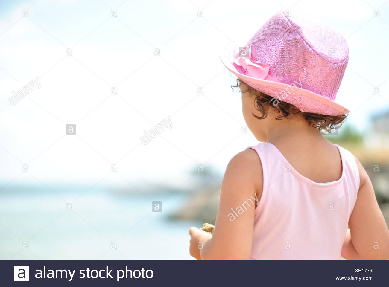 Rear view of a girl looking out to sea - Stock Image