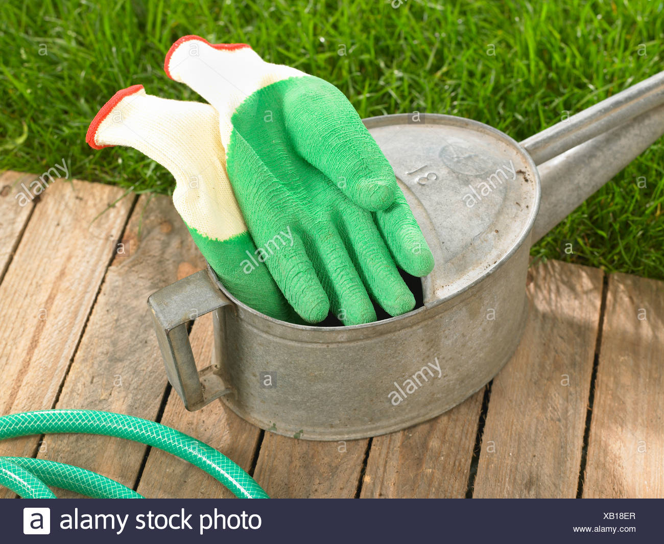 Pair of gardening gloves with a watering can - Stock Image