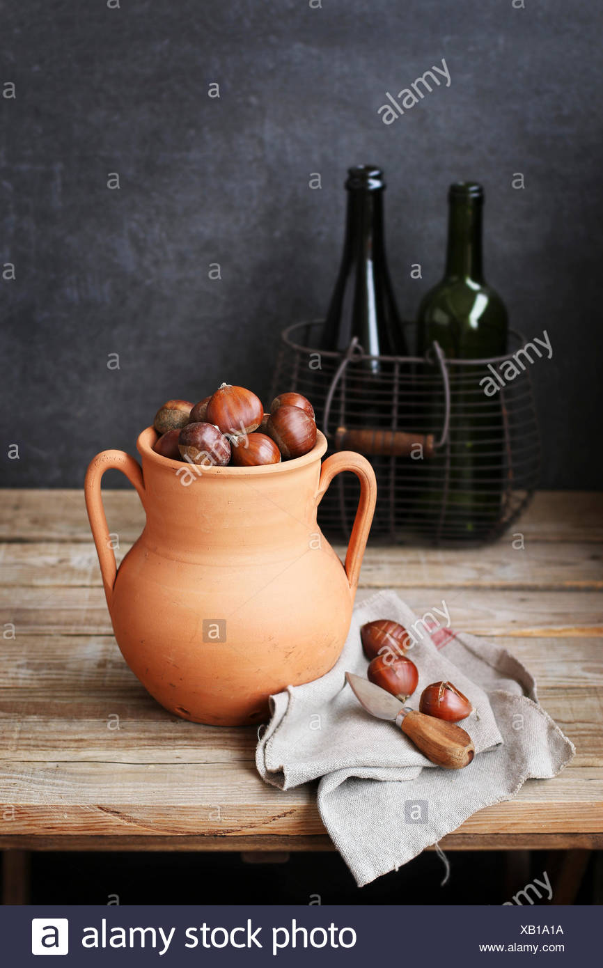 Chestnuts in a rustic clay roaster with two empty bottles in a wire basket on background - Stock Image