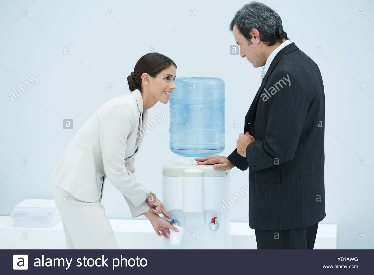 Two professionals chatting beside water cooler, woman filling disposable cup - Stock Image