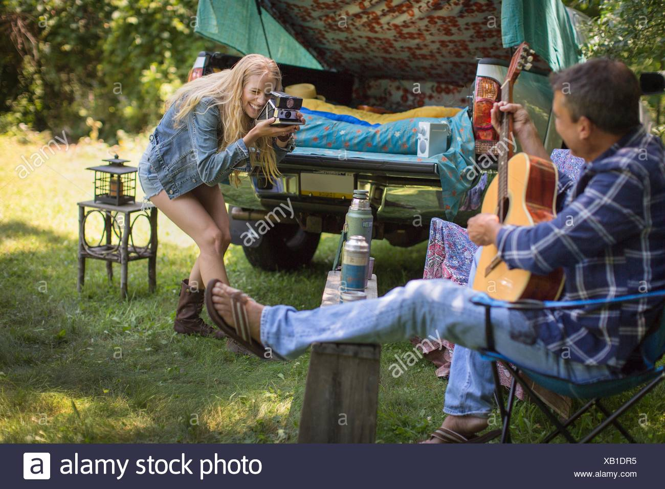 Young woman photographing boyfriend playing acoustic guitar whilst camping - Stock Image