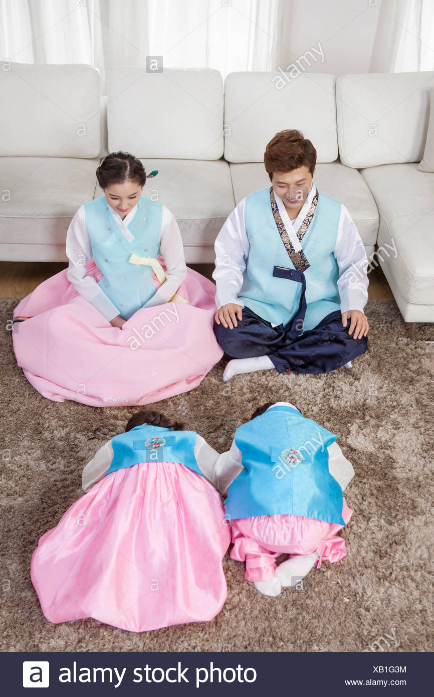 Korean son and daughter sitting and bowing to their parents on traditional Korean holiday - Stock Image