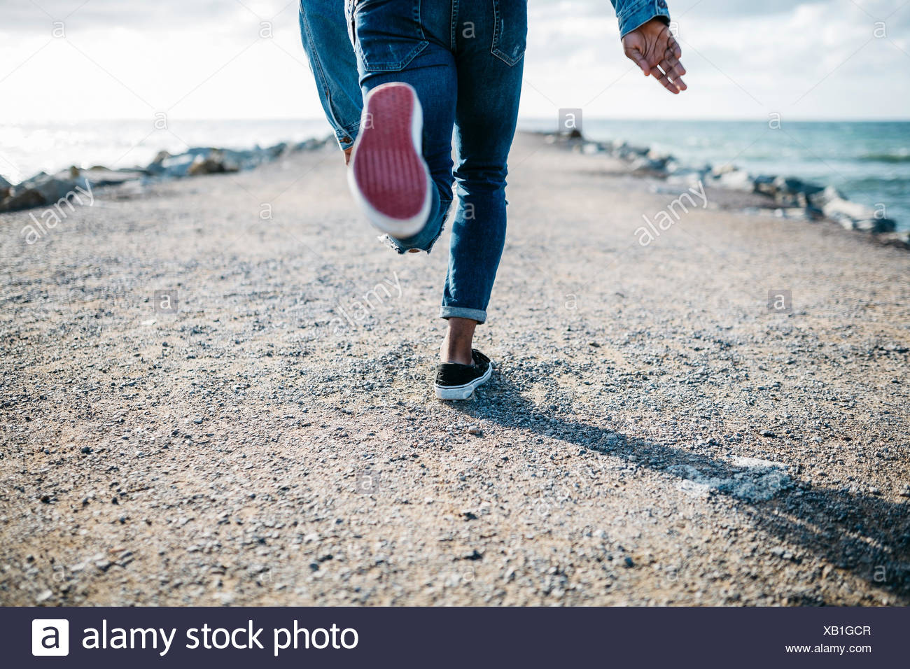 Legs of young man running on jetty - Stock Image