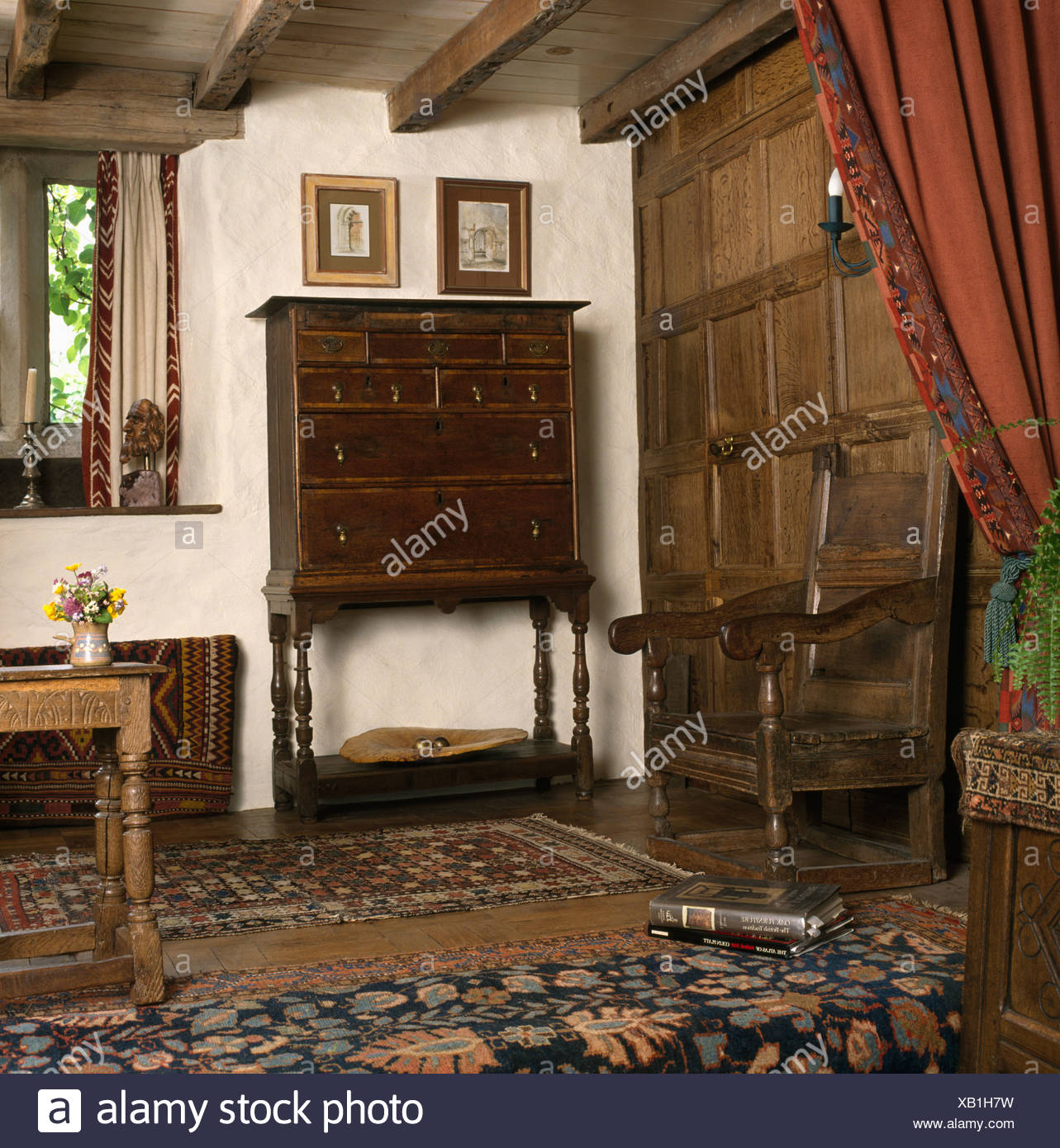 Oak paneling and antique oak Jacobean chair and chest-on-stand in country living room Stock Photo