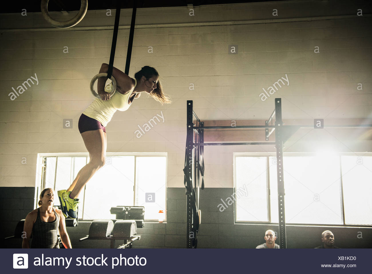 Young woman on gymnasium rings watched by trainer - Stock Image