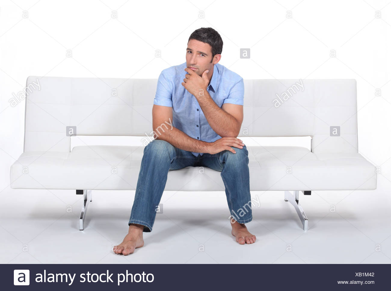 Man sitting on a sofa - Stock Image