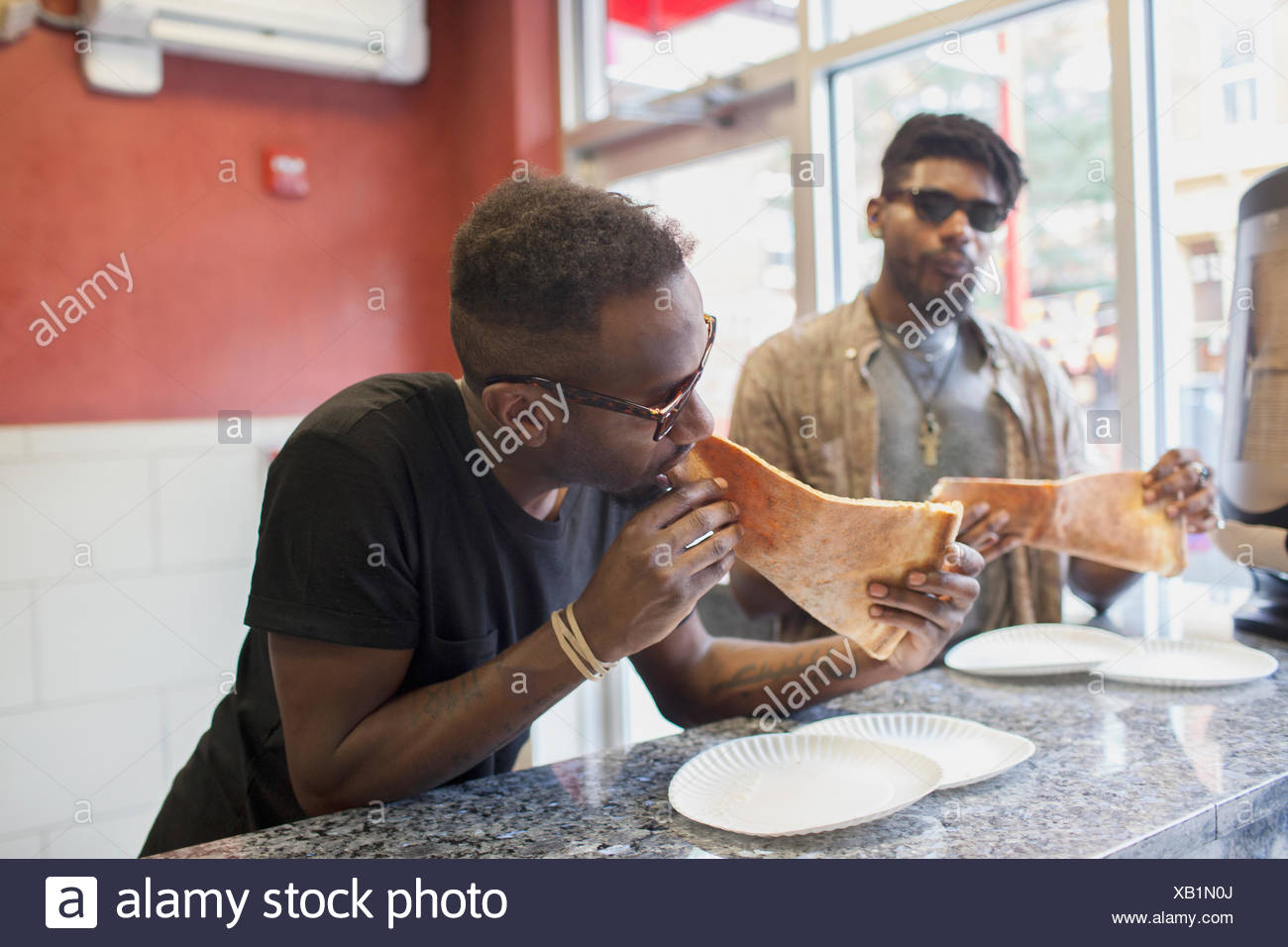 Two young men eating pizza. - Stock Image