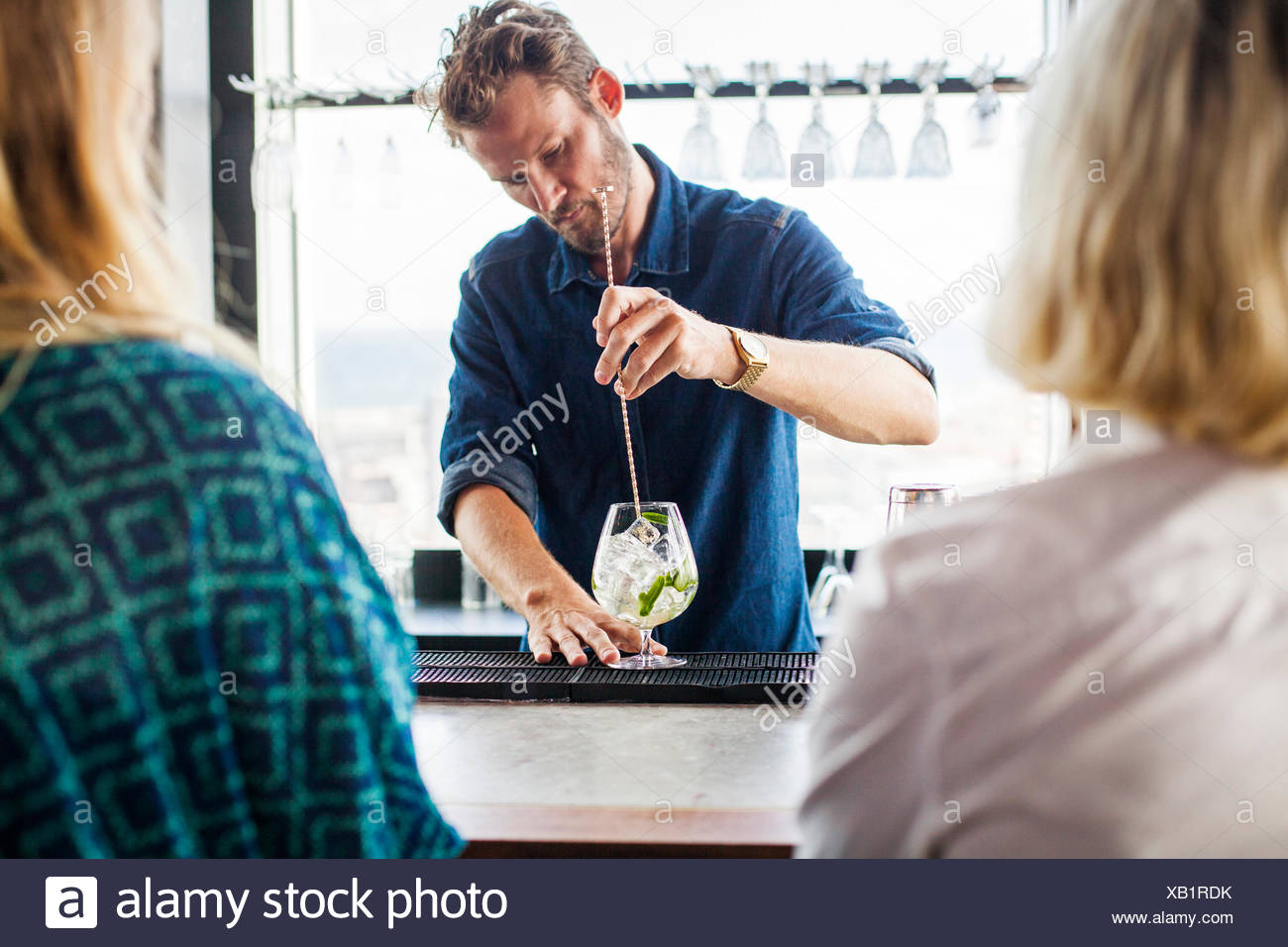 Female customers with bartender making drink at bar counter - Stock Image