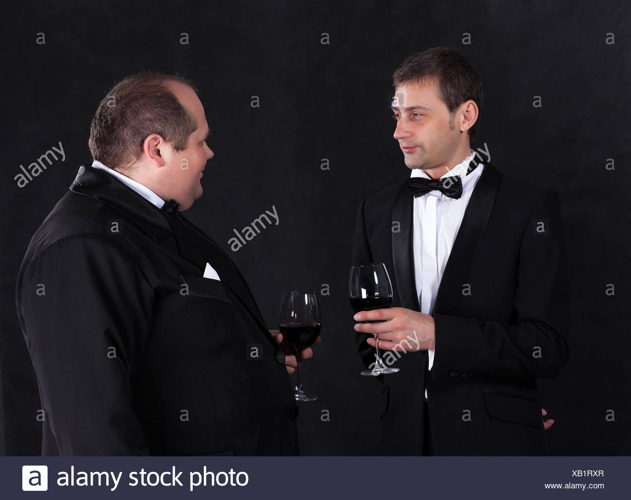 Two stylish businessman in tuxedos with glasses of red wine - Stock Image