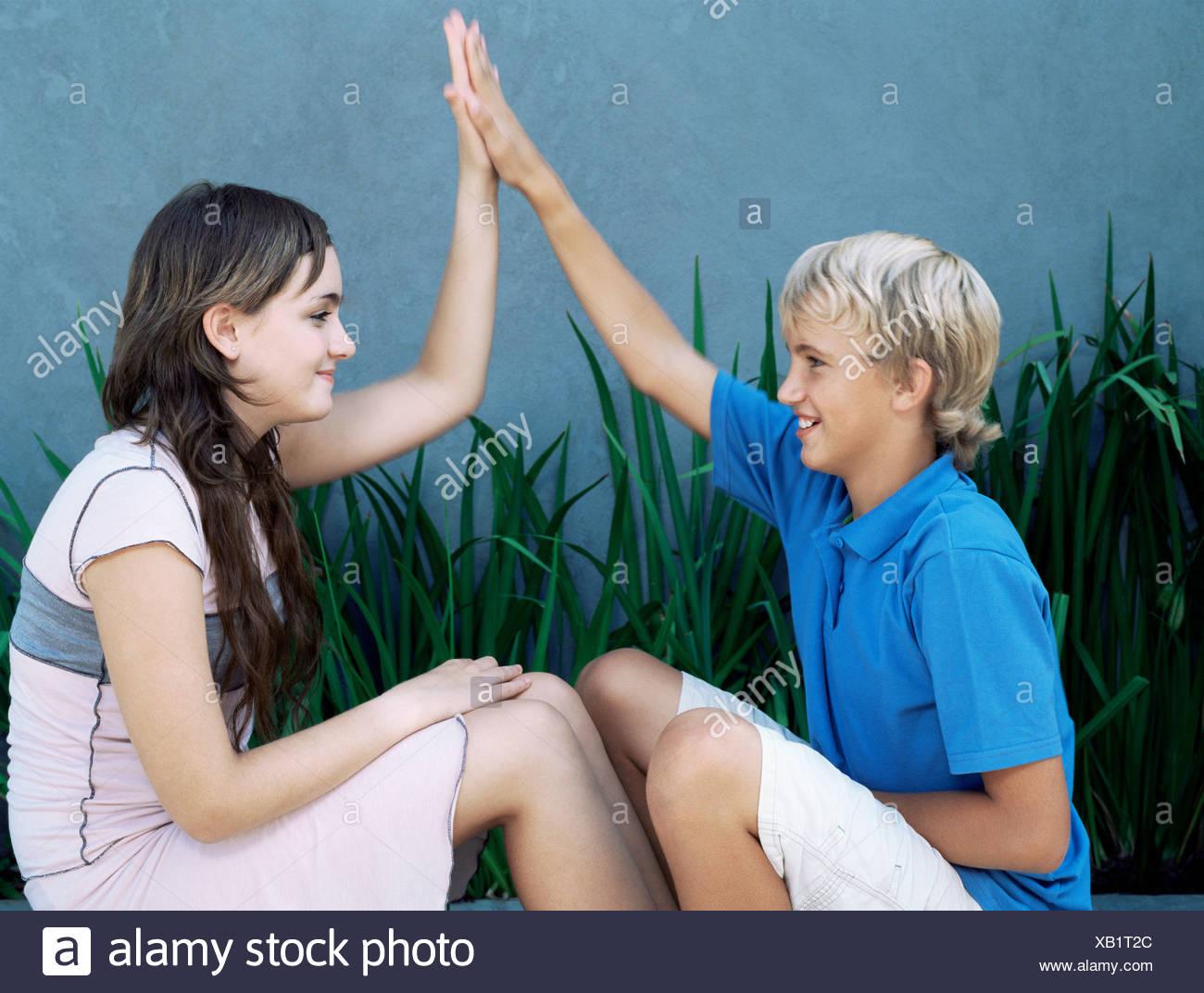 Boy and girl doing high five - Stock Image