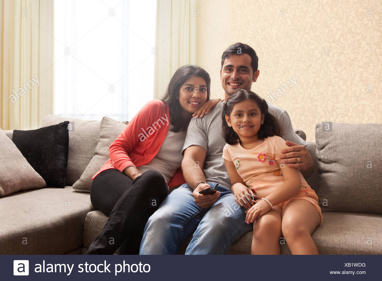 Happy family watching TV at home - Stock Image