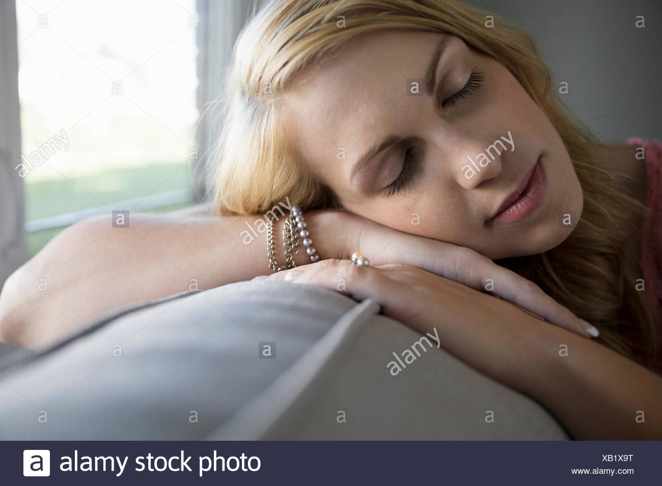 Serene woman sleeping on sofa - Stock Image