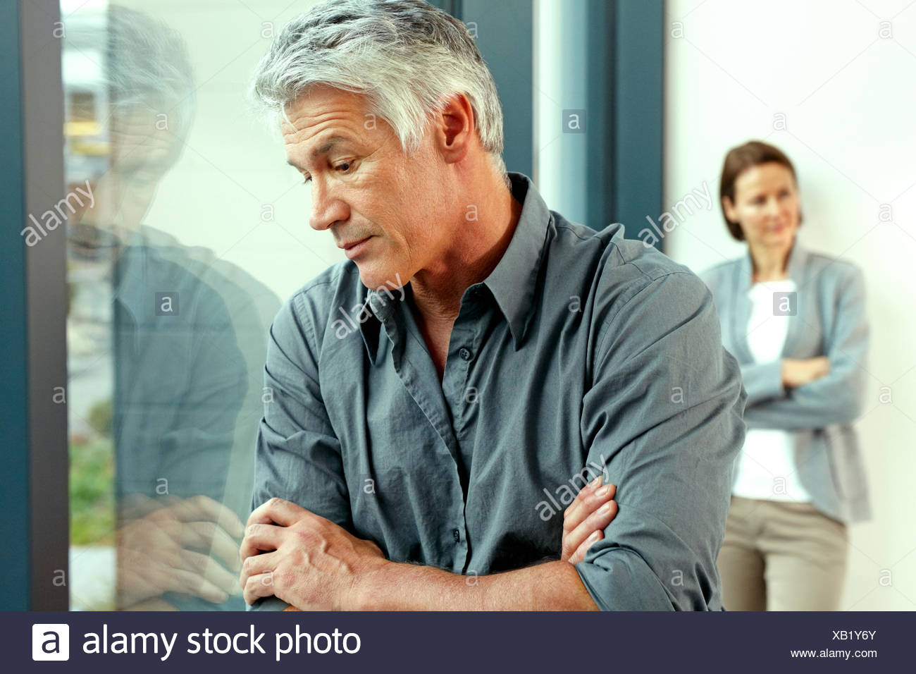 Portrait of unhappy man with his his wife standing in the background Stock Photo