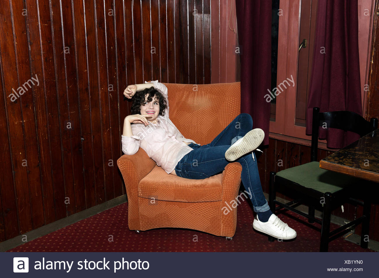 Portrait of young woman reclining on armchair on night out in bar - Stock Image