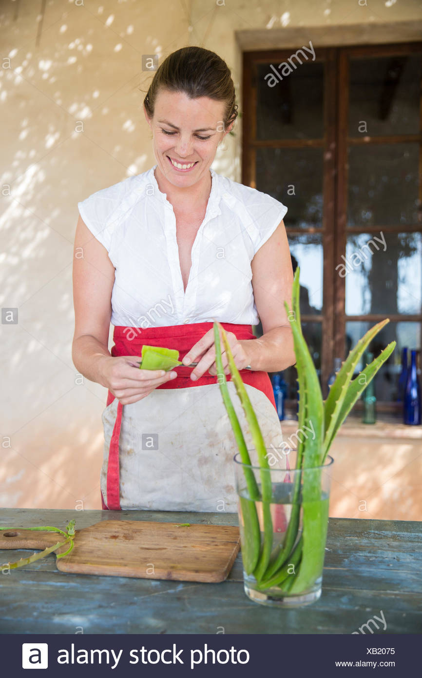 Woman scraping liquid from aloe leaf in handmade soap workshop - Stock Image