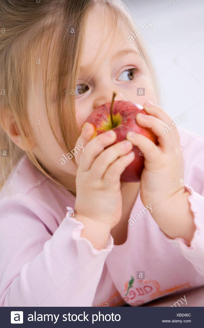 Little girl (3-4) holding an apple, portrait - Stock Image