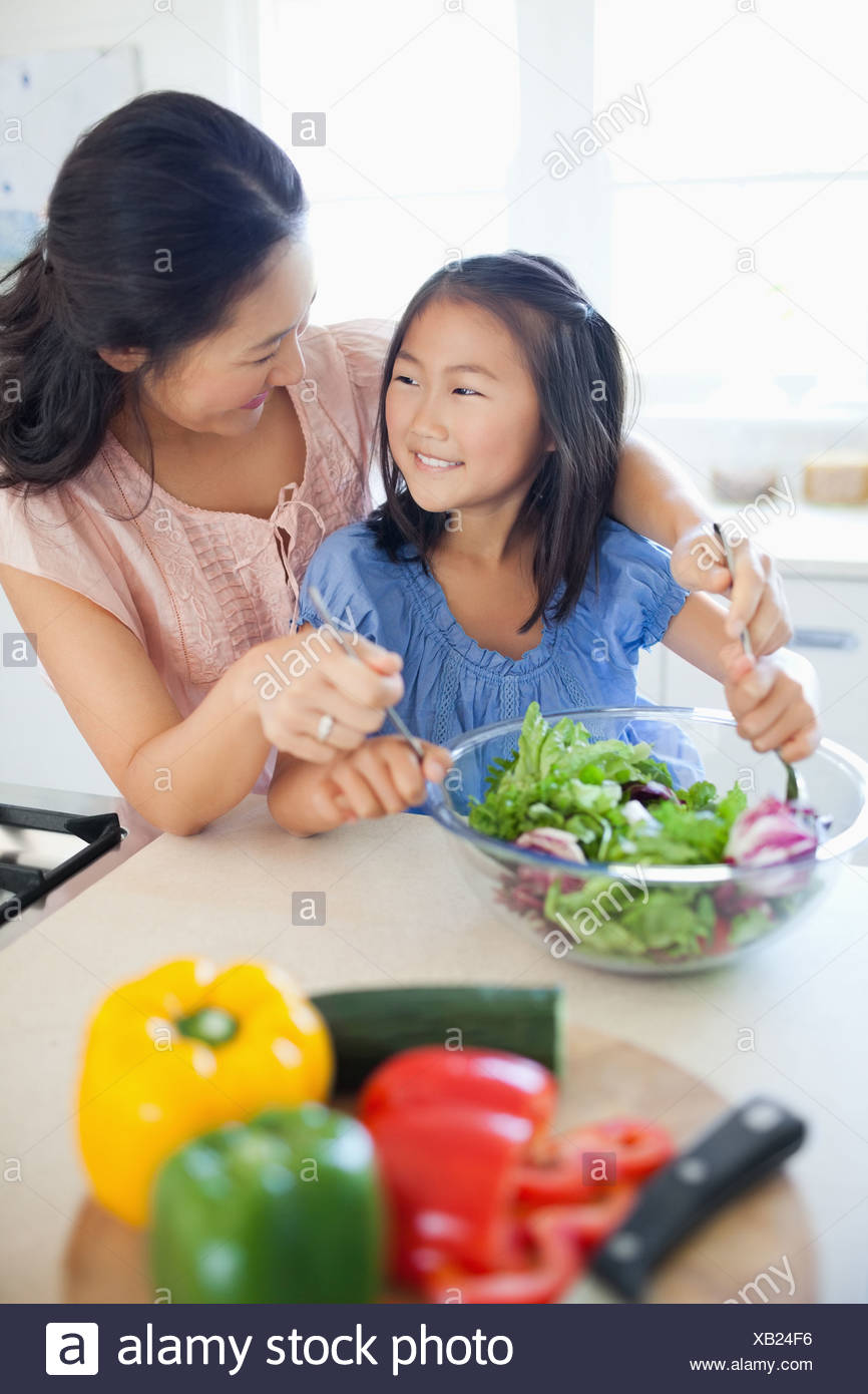 A mother looks at her daughter as they smile and toss a salad - Stock Image