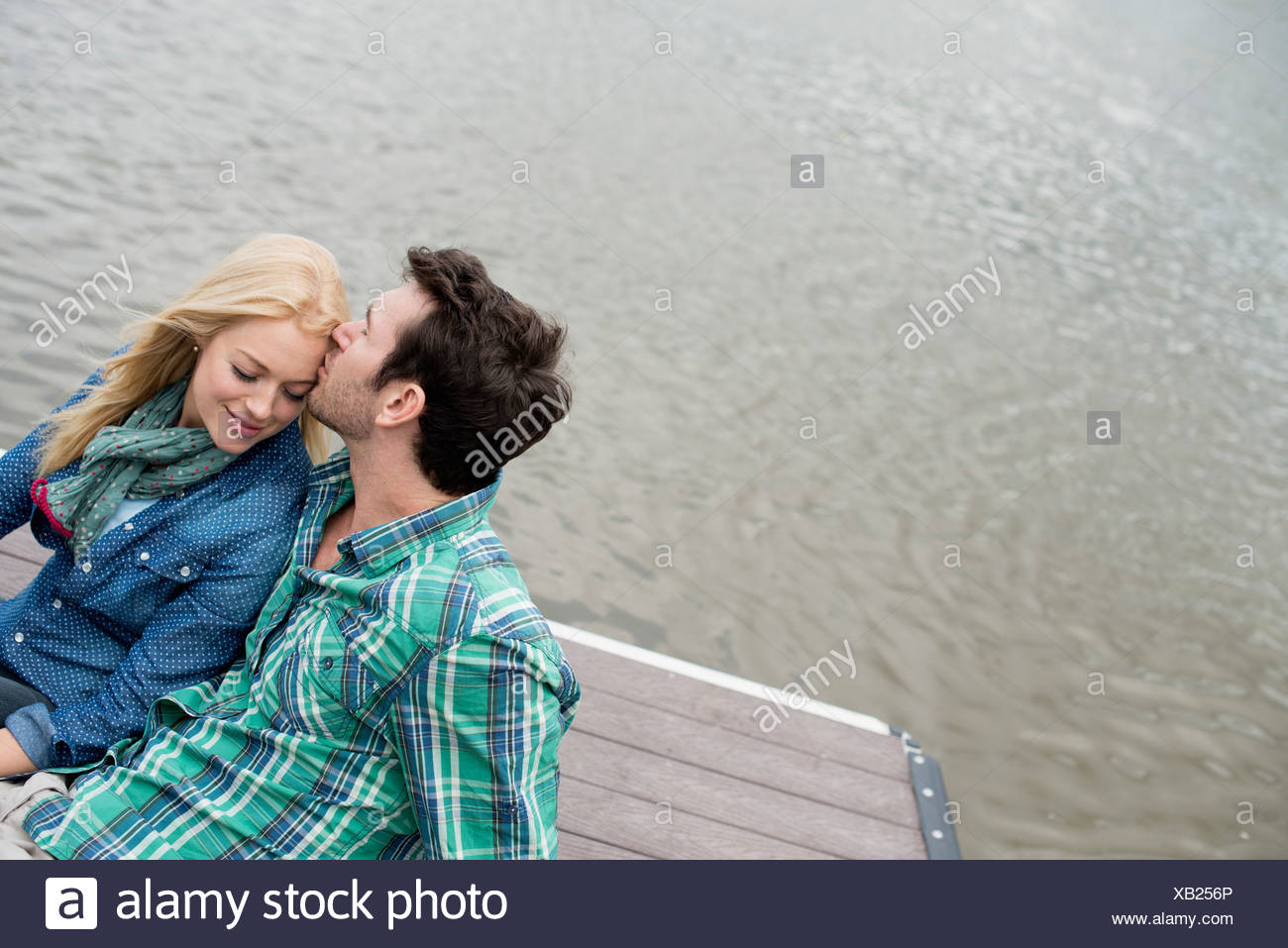 A man and woman seated on a jetty by a lake. - Stock Image