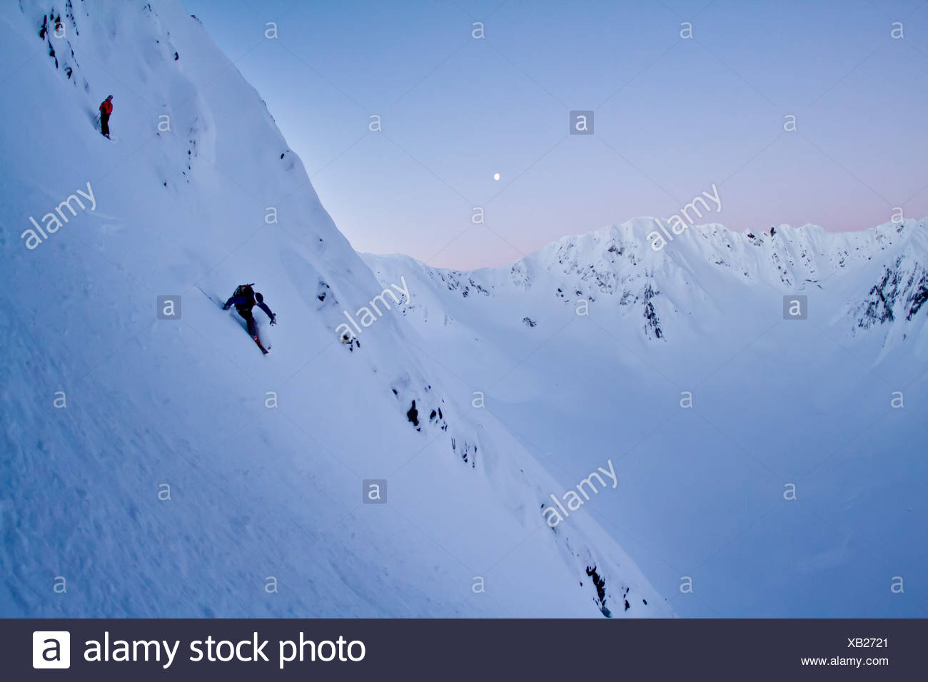 Skier and his spotter skiing steep powder on the north side of Kickstep Mountain, Turnagain Pass, Kenai Mountains, Alaska. MR - Stock Image